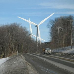 Featured: Car on a dirty snowy road with giant wind turbines in the distance